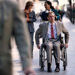 Мужчина в костюме и инвалидном кресле